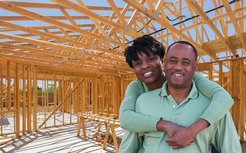 Black couple smiling in front of new home construction