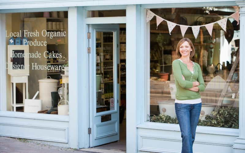 Woman standing in front of her business storefront