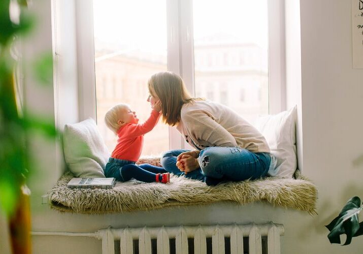 Mother and toddler sitting on window bench